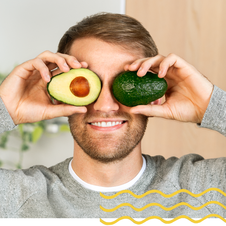 Person holding an avocado up to his eyes