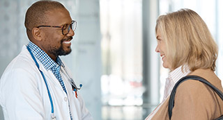 Photo of psoriasis patient and dermatologist engaged in conversation